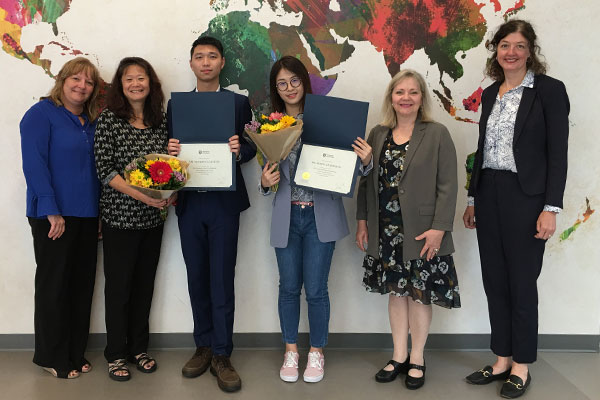 group standing in front of map with flowers and awards