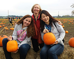 Homestay host and two students in pumpkin patch