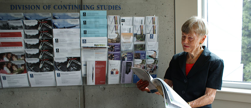 Photograph of Nan Walmsley looking at a course calendar.