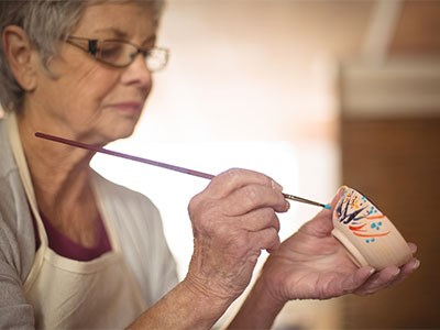 Photo of a senior citizen painting a bowl