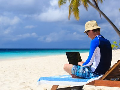Photo of student working on laptop at the beach