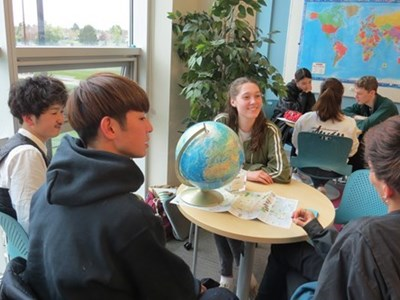 Photo of students around a globe at the ELC