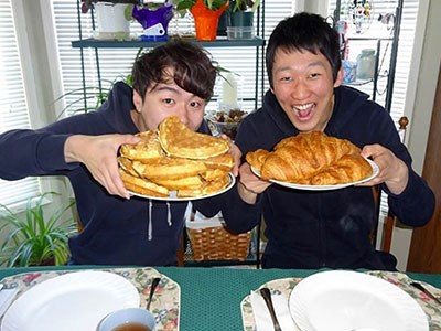 Photo of two homestay students holding up large quantities of breakfast foods